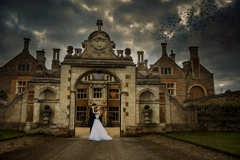 fine art wedding photography of bride and groom in front on Holdenby House on their wedding day