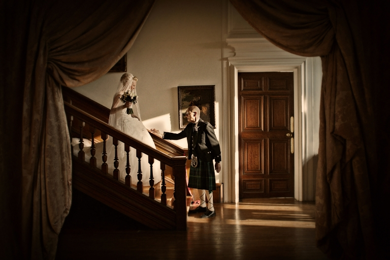 fine art reportage wedding photography of bride and father on staircase at Holdenby House wedding